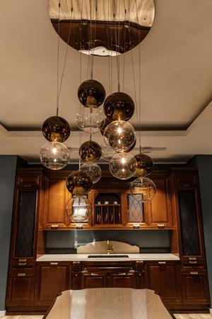 Shiny spherical chandelier over elegant wooden counter in kitchen 写真素材