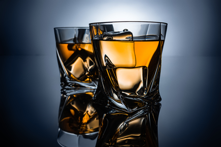 two glasses of whiskey with ice cubes, on dark grey background
