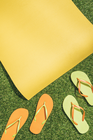 flat lay with yellow mat and flip flops on green grass