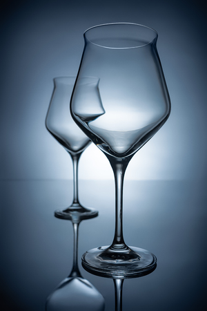 two empty transparent wine glasses on grey with reflections Stock Photo