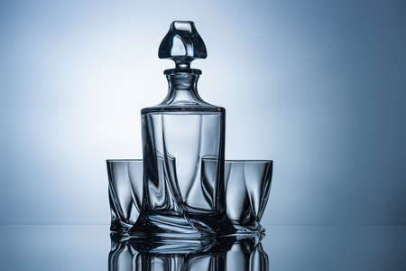 whiskey glasses and empty bottle on grey with reflection