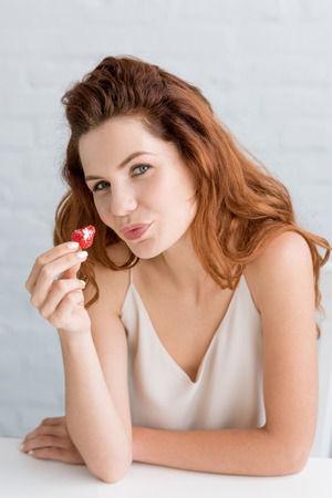 close-up portrait of happy young woman eating strawberry