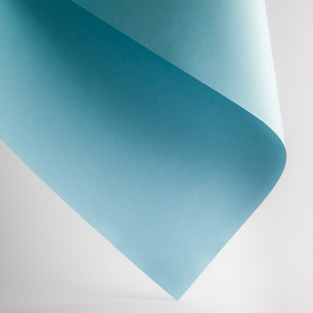 colored blue paper sheet on grey background