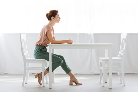 side view of attractive young woman sitting at table alone at home Stock fotó