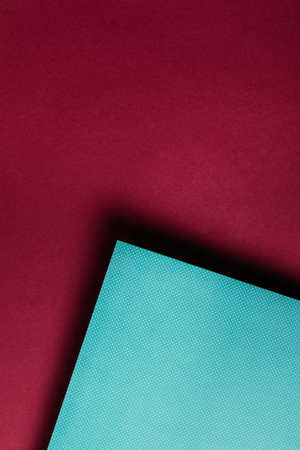 creative turquoise paper sheet on grungy maroon background 版權商用圖片