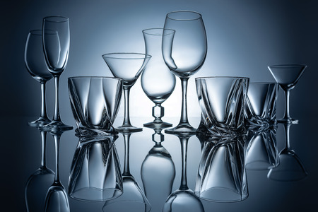 martini, cognac, champagne and wine empty glasses with reflections on grey