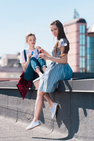 two young female friends using bubble blowers at rooftop Stock Photo