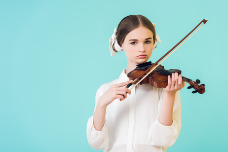 stylish teen girl playing violin, isolated on blue