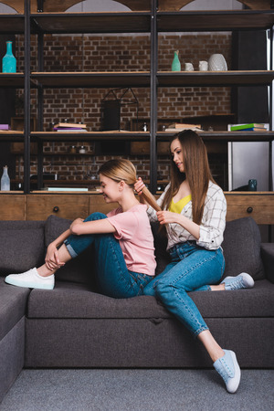 young woman hairdressing female friend on sofa at home
