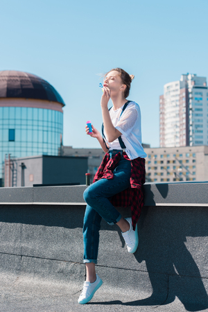 young woman using bubble blower at rooftop
