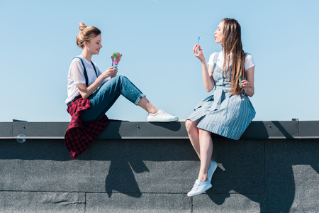 side view of two female friends using bubble blowers at rooftop Stock Photo