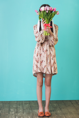 stylish girl in summer dress holding tulips, on blue