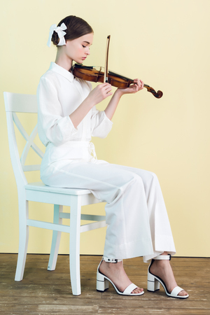 teenager in white outfit playing violin and sitting on chair