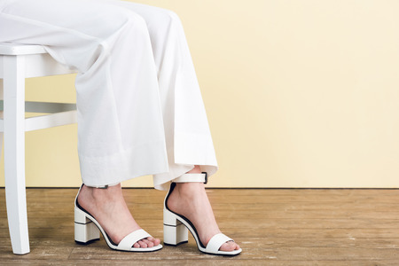 cropped view of fashionable woman in white pants and sandals sitting on chair Standard-Bild - 106604473