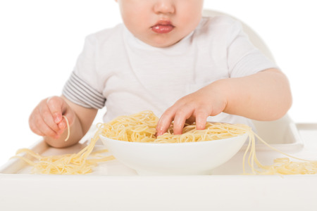 cropped shot of baby boy eating spaghetti by hands and sitting in highchair Stock Photo - 106604682