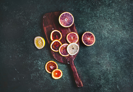 top view of cutting board with slices of blood orange and lemon on table Фото со стока
