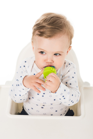 high angle view of little boy with baby pacifier sitting in highchair isolated on white background Stock Photo - 106609517