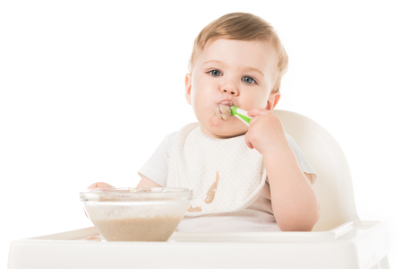 little boy in bib eating porridge by spoon and sitting in highchair isolated on white background