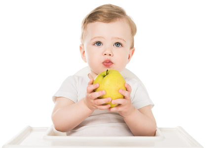baby boy holding apple and sitting in highchair isolated on white background Stock Photo - 106609526