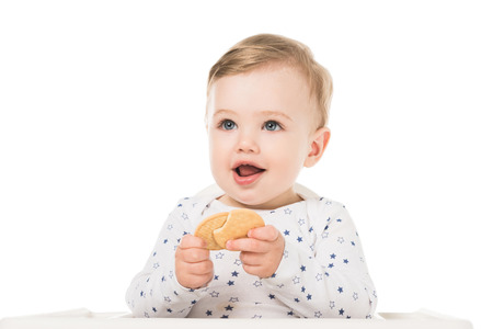 smiling little boy with cookies sitting in highchair isolated on white background Stock Photo