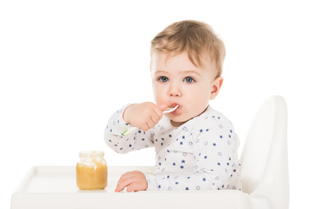 adorable baby boy eating puree from jar and sitting in highchair isolated on white background Stock Photo - 106604655