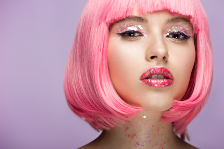 attractive woman with pink hair and bright glittering makeup looking at camera isolated on violet