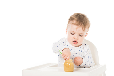 little boy eating puree from jar and sitting in highchair isolated on white background Stock Photo - 106604667