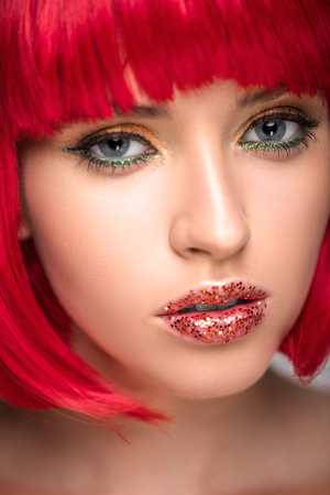 headshot of attractive woman with red hair and sparkling makeup looking at camera Stock Photo