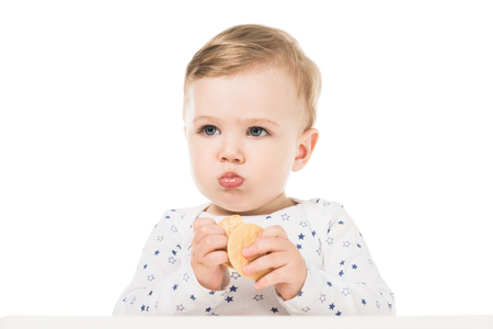 adorable little boy eating cookies and sitting in highchair isolated on white background Stock Photo