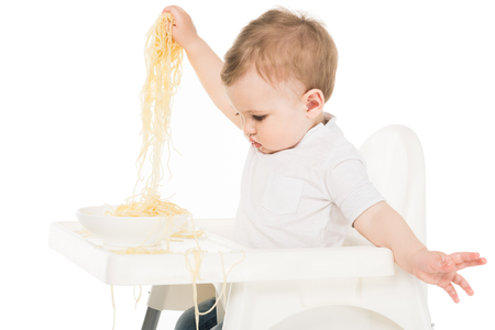 baby boy holding spaghetti in hands and sitting in highchair isolated on white background Stock Photo - 106609222