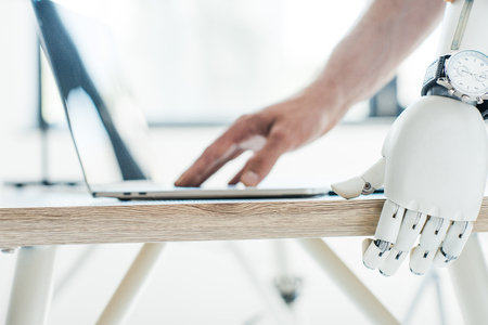 close-up view of robotic arm with wristwatch leaning at wooden table and human hand using laptop