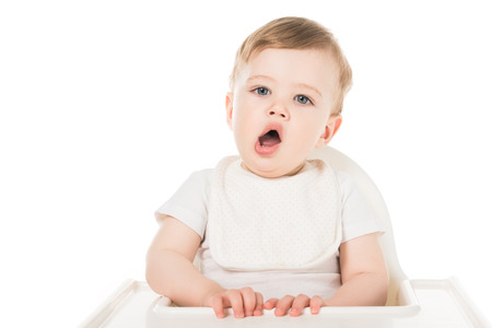 yawning baby boy in bib sitting in highchair isolated on white background Stock Photo - 106609500