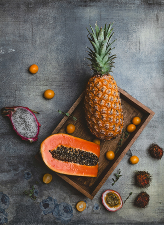 top view of kumquats, pitaya, papaya, rambutans, passion fruit and pineapple on table 스톡 콘텐츠
