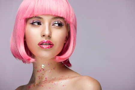 beautiful woman with pink hair and makeup with glitter looking away isolated on violet 免版税图像