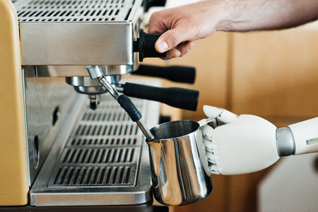 close-up view of robotic arm and human hand preparing coffee in coffee machine