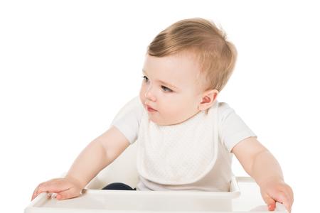 Adorable petit garçon en bavoir assis en chaise haute isolé sur fond blanc