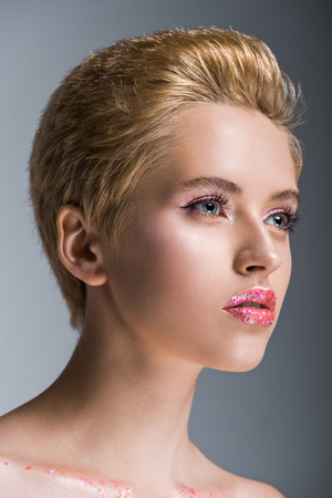 attractive woman with short hair and makeup looking away isolated on grey