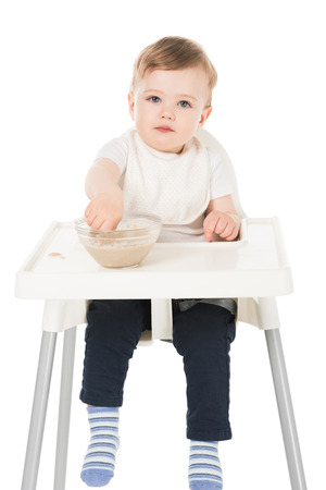 little boy in bib eating puree and sitting in highchair isolated on white background Stock Photo - 106610400