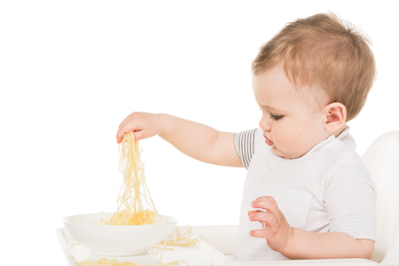 side view of adorable little boy eating spaghetti by hand isolated on white background