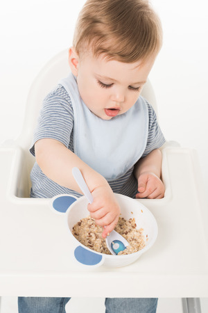 high angle view of baby boy in bib eating and sitting highchair isolated on white background Stock Photo - 106610464