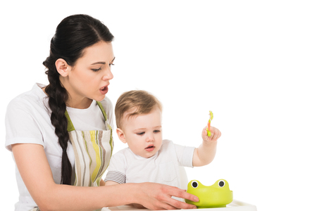 angry mother in apron trying to feed little son sitting in highchair isolated on white background Stock Photo