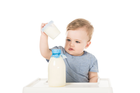 little boy with plastic container and bottle of milk and sitting in highchair isolated on white background