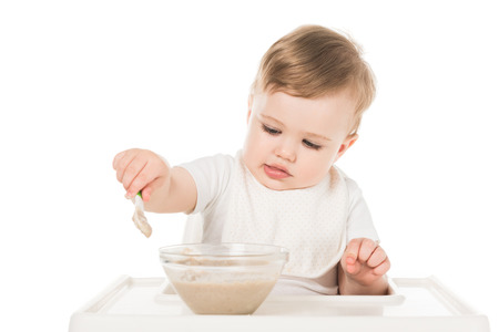 little boy in bib eating baby food by spoon and sitting in highchair isolated on white background