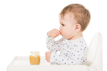 side view of baby boy eating puree from jar and sitting in highchair isolated on white background