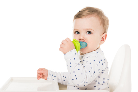 little boy with baby pacifier sitting in highchair isolated on white background 스톡 콘텐츠