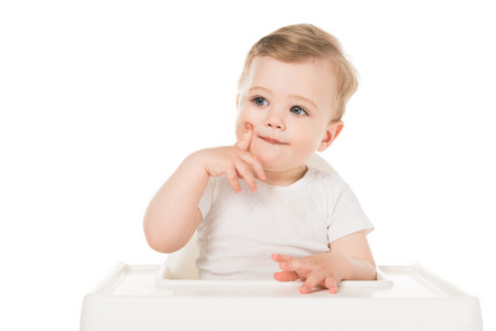adorable little boy sitting in highchair isolated on white background Stock Photo - 106610747