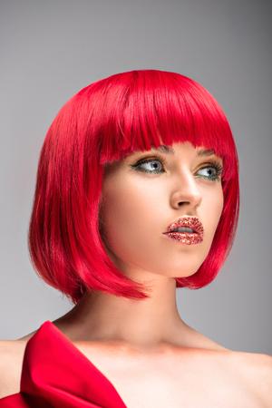 niedrige Winkelansicht der attraktiven Frau mit den roten Haaren und dem Glitzer auf dem Gesicht, das lokal auf grau wegschaut