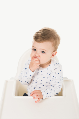 high angle view of eating baby boy sitting in highchair isolated on white background Stock Photo - 106610646