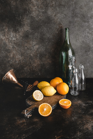cutting board, different bottles, oranges, lemons, funnel and wooden squeezer on marble table
