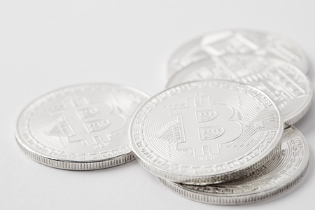 close-up shot of heap of bitcoins lying on white surface